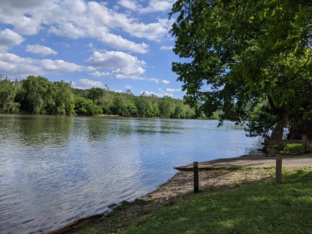 A view from the riverbank of the New River next to the boat launch on a sunny summer day.